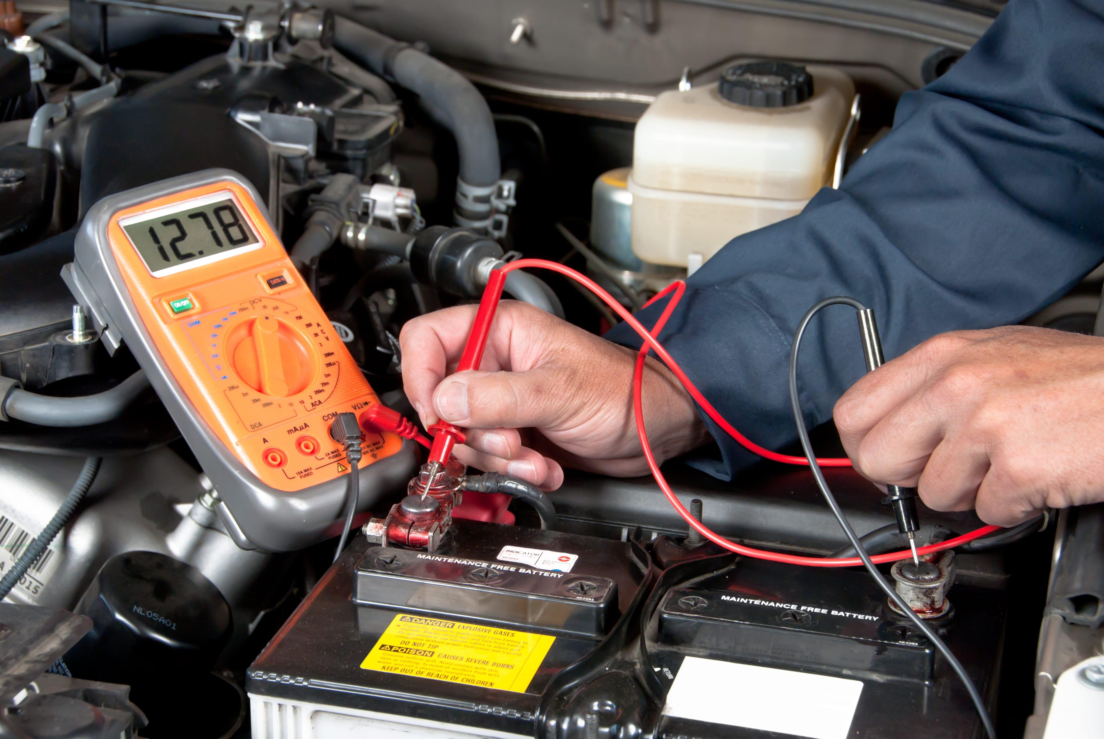 auto mechanic checking car battery voltage BGULM3J